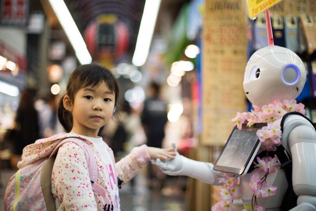 Une petite fille donne la main d'un robot doté d'intelligence artificielle